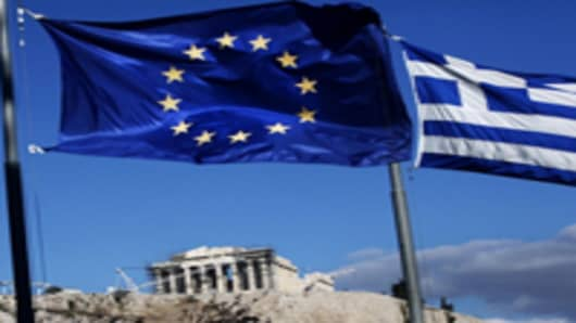 The European Union and Greek national flags fly near the Parthenon temple on Acropolis hill in Athens, Greece.