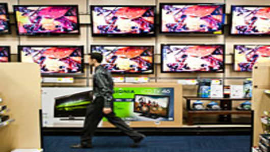 A salesman passes In front televisions displayed for sale at a Best Buy store in New York.