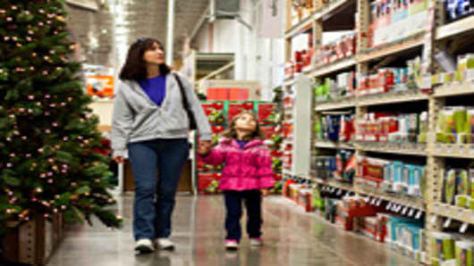 Customer Lynn Leonard, left, and her daughter Meghan Leonard, 4, walk through the holiday decorations area at a Home Depot Inc. store in Charlotte, North Carolina.