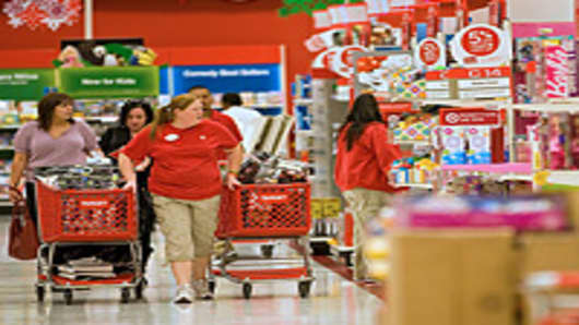 Target Corp. employees restock merchandise while customers shop at a Super Target store in Denver, Colorado.