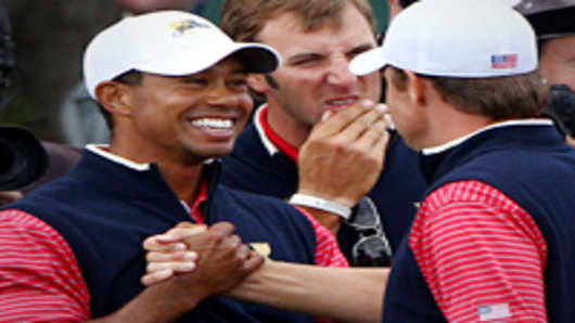 Tiger Woods of the U.S. Team shakes hands with Nick Watney of the U.S. Team after winning his match on the 15th hole during the Day Four Singles Matches of the 2011 Presidents Cup