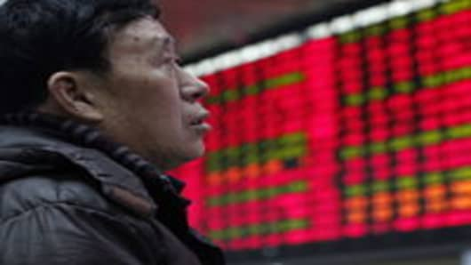 An investor watches the electronic board at the stock exchange in Shanghai, China.