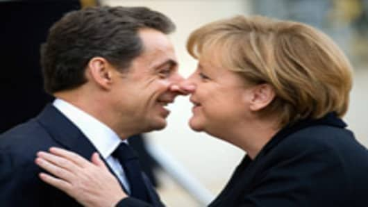 French President Nicolas Sarkozy welcomes German Chancellor Angela Merkel prior to a working lunch at the Elysee Palace in Paris.