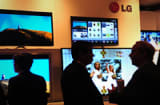 People mingle in front of a display of LG Electronics televisions.