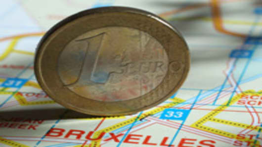A one Euro coin stands on a map of Brussels
