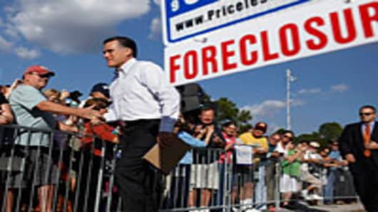 Mitt Romney greets supporters as he arrives for a campaign event in front of a foreclosed home January 24, 2012 in Lehigh Acres, Florida.