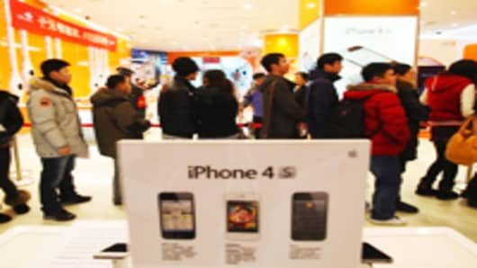 Chinese people line up to buy iPhone 4S in a China Unicom store in Beijing, China.