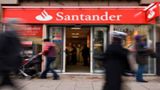 """Shoppers pass a branch of the newly-branded Santander bank on Oxford Street, in central London, on January 11, 2010. Spanish banking giant Santander on Monday declared that it wants to become Britain's biggest bank, as it began rebranding its British operations with its own name. Chairman Emilio Botin said that the ambitious group """"wants to be the number one bank in the UK"""" and may buy more assets from struggling rivals. Botin told a London press conference that the Madrid-based banking titan wo"""
