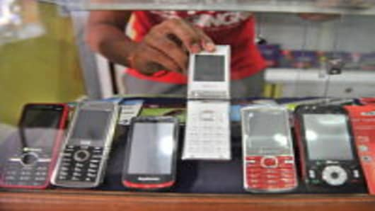 An Indian shopkeeper shows China Mobile phones in his mobile phone outlet in Hyderabad on January 5, 2012. Indian customers seek cheap products which are only available in China. Bilateral trade between the two Asian economic giants has grown from just 2.33 billion USD in 2000-01 to 60 billion USD in 2010 and is expected to touch 100 billion USD by 2015.