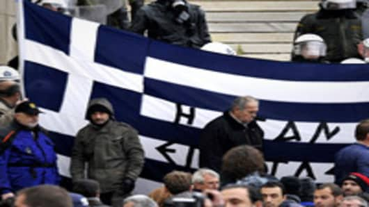 Protesters hold a Greek flag at the steps of the parliament during a 24-hours general strike in Athens.