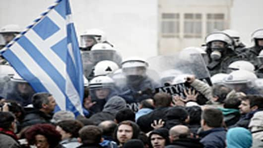 Protesters clash with riot police while they try to enter the parliament during a 24-hours general strike in Athens.