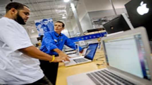 Marc White, left, asks Best Buy employee Steve Buckner questions about an Apple MacBook Pro laptop computer at a Best Buy store in Atlanta, Georgia, U.S.
