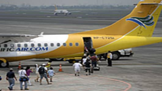 Tourists walk on the tarmac towards a Cebu Pacific jet bound for Catiklan at the terminal 3 of the Ninoy Aquino International Airport in Manila