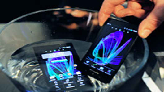 An employee uses a bowl of water to demonstrate the waterproof properties of Panasonic Corp. Eluga smartphones at the Mobile World Congress in Barcelona, Spain, on Tuesday, Feb. 28, 2012.