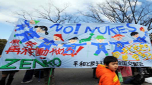 A boy walks in front of a huge anti-nuclear banner during a protest rally in Tokyo In February, 2012.