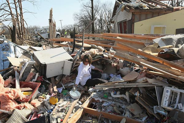 Kristin Allen searches for valuables in her mother's home after it was destroyed by a tornado in Harrisburg, Illinois.
