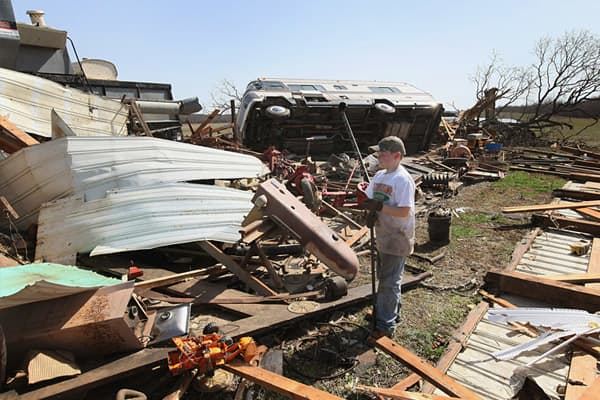 Ethan Parks help to salvage items after a tornado destroyed the barn on the farm of his great-great uncle on March 1, 2012 near Harrisburg, Illinois.