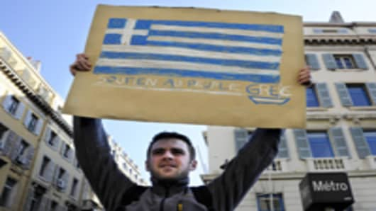 A man holds a placard bearing the Greek flag.