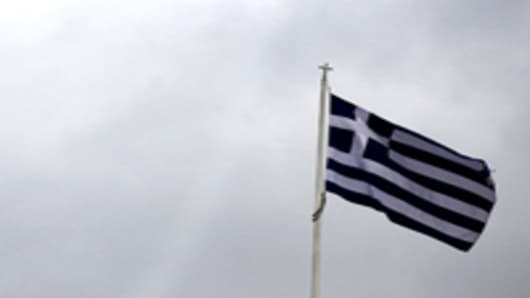 The Greek national flag is seen flying above the parliament building on Syntagma Square in Athens, Greece, on Thursday, Feb. 16, 2012.