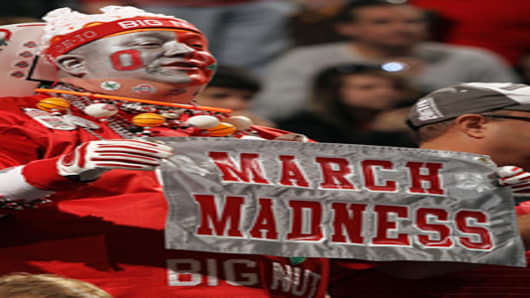 John 'Big Nut' Peters, fan of the Ohio State Buckeyes, holds up a sign which reads 'March Madness' against the Michigan State Spartans during the Final Game of the 2012 Big Ten Men's Conference Basketball Tournament.