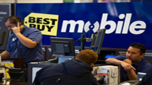 Employees help customers at a Best Buy store.