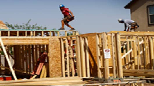 A construction worker walks on the roof of a new home being built in Phoenix, Arizona.