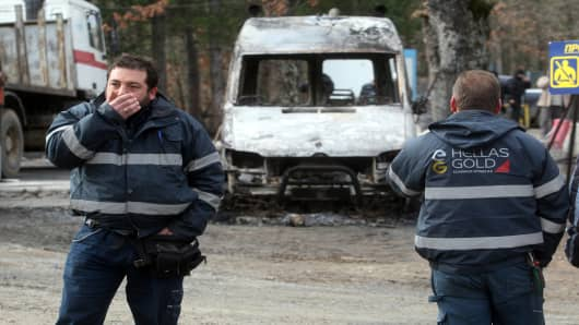 Workers of the Hellenic Gold company walk in a lot among burned-out cars in the forest of Skouries. Dozens of hooded men firebombed the premises, injuring a guard and damaging containers, cars and trucks.