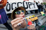 Katie, a college graduate, blows bubbles during an Occupy Wall Street rally against the high cost of college tuitions on April 25, 2012 in New York.