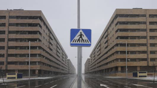 A road sign stands between blocks of empty apartments at Francisco Hernando village at the Sesena real estate development near Madrid.Out of 13,000 apartments that were meant to make up the development of Sesena only 5,100 were built, many of which are now uninhabited with those Spaniards who bought them as investments trying to sell them off for huge losses.One is example is Juan Carlos Caballero who bought an apartment in Sesena in 2008 for 185,000 euros alongside his father who had previously