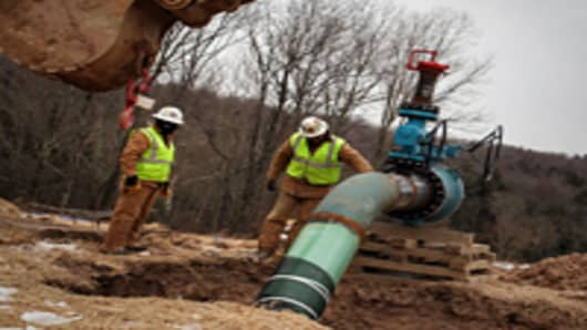 Men work on a natural gas valve at a hydraulic fracturing site.