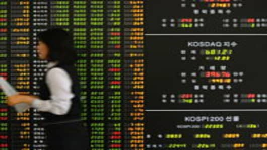 An employee of a securities company walks past a stock index board in Seoul, South Korea