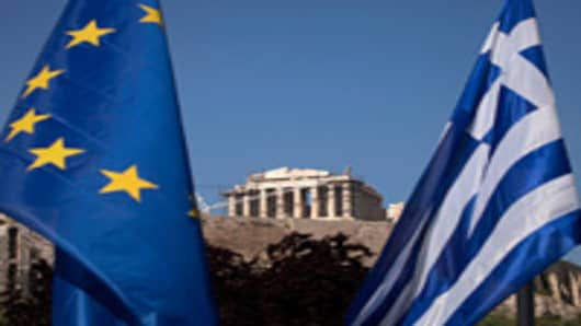 A European Union flag, left, hangs beside a Greek national flag beneath the Parthenon temple on Acropolis hill in Athens, Greece.