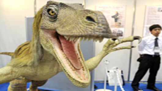 A robotic Velociraptor dinosaur opens its mouth to scare visitors as it demonstrates the power of air pressure at the fluid power exhibition in Tokyo.