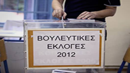 A voter places his sealed and stamped ballot paper into a ballot box in the second round of the Greek general elections, at a polling station in Athens, Greece.