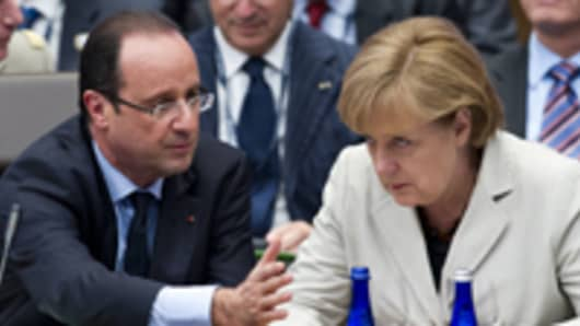 French President Francois Hollande (L) speaks with German Chancellor Angela Merkel (R)