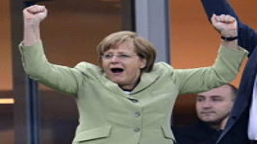 German Chancellor Angela Merkel celebrates after Philip Lahm scored against Greece during the Euro 2012 football championships quarter-final match.