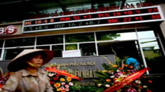 Stock prices are shown on a ticker outside a securities firm in Hanoi, Vietnam