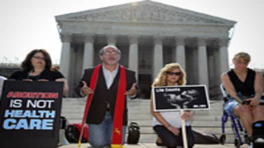 Pro-life activists, led by Rev. Pat Mahoney (2nd L) of Christian Defense Coalition, pray in front of the U.S. Supreme Court in Washington, DC.