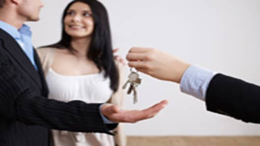 Young couple with keys to house