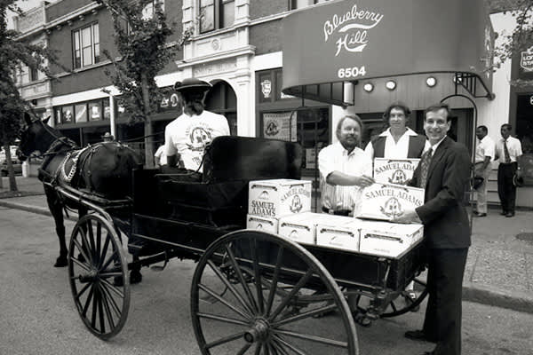 "Koch hired a horse and carriage to help deliver the first cases of Sam Adams on Patriots' Day in 1984.But for the most part, he kept his costs low during the early days. ""It was started on a shoe string,"" said Koch, who raised about $240,000 from friends, family and personal savings to launch the business.The company didn't have an office for the first six to seven months. Nor did it have a computer. Koch made calls from pay phones and held meetings at bars. For the first year, he stored and kep"