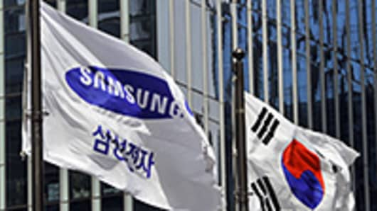 Samsung Electronics flag and South Korean flag (R) flutter outside its headquarters in Seoul.