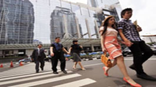 Pedestrians cross a street in Jakarta's modern business district.