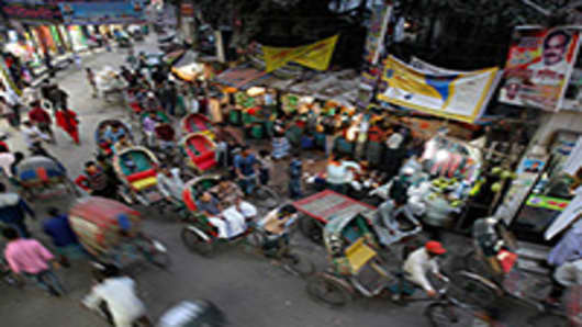Pedestrians and rickshaws move along a street in the Old Market of Dhaka, Bangladesh.