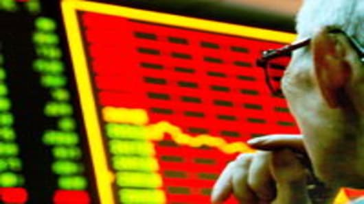 An anxious local investor looks at the stock index display screen of shares in trading at a stock exchange on June 7, 2006, in Zhengzhou, Henan Province China.