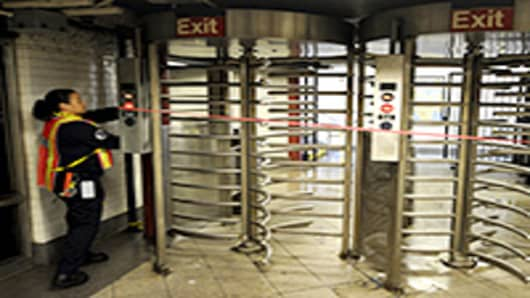 An MTA worker lockes up a gate at Union Square station.