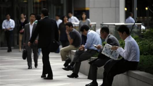 Japanese office workers rest at a business district in Tokyo.