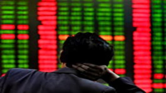 A Chinese investor monitors screens showing stock indexes at a trading house in Shanghai on June 1, 2010.