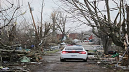 A police car drives down a tornado-ravaged street March 3, 2012 in Henryville, Indiana. Dozens of people were killed as severe weather and tornados ripped through the South and Midwest on March 02, 2012.