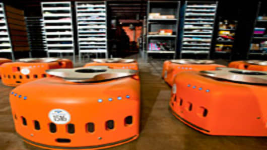 Kiva Systems Inc. robots sit at an Acumen Brands Inc. warehouse in Fayetteville, Arkansas, U.S., on Friday, Aug. 12, 2011. Kiva has seen orders for its warehouse robots surge this year as brick-and-mortar retailers rush to open distribution centers to compete with online mercha