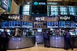 Traders work at a Knight Capital Group Inc. post on the floor of the New York Stock Exchange.